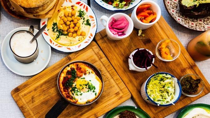 Hummus, Pitabrot, verschiedene Dips und Salat auf Holzbrettern und Tellern