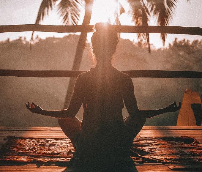 Frau meditiert mit Blick auf die Sonne