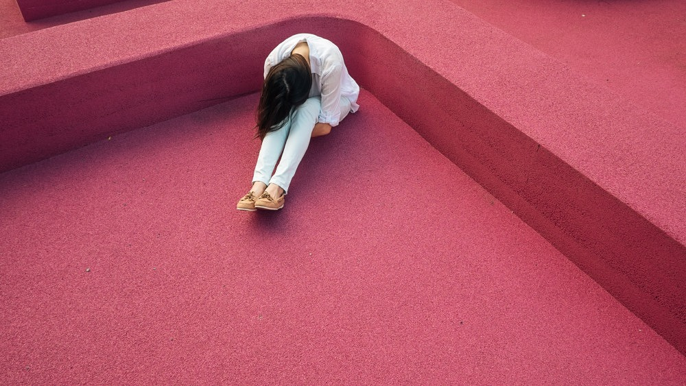 Traurige Frau mit braunen Haaren, die auf dem Boden sitzt und ihr Gesicht im Schoß vergräbt.