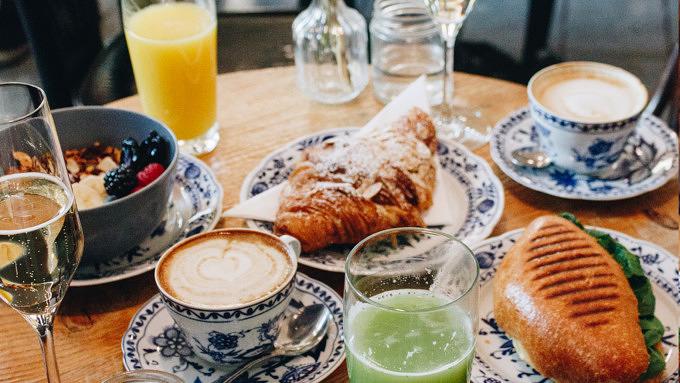 Frühstückstisch im La Maison mit Granola, Mandelcroissant und Tuna Melt Sandwich