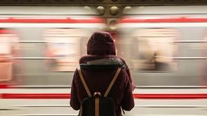 Frau wartet vor einem vorbeifahrenden Nachtzug von Berlin nach Wien