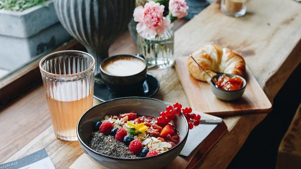 Eine Bowl mit Porridge und Obstkompott, ein Croissant mit hausgemachter Marmelade, Cappuccino und eine Rhabarberschorle