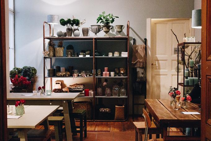 Der hintere Raum vom Café Schöngrau mit Wohnaccessoires, Blumen und Kerzen