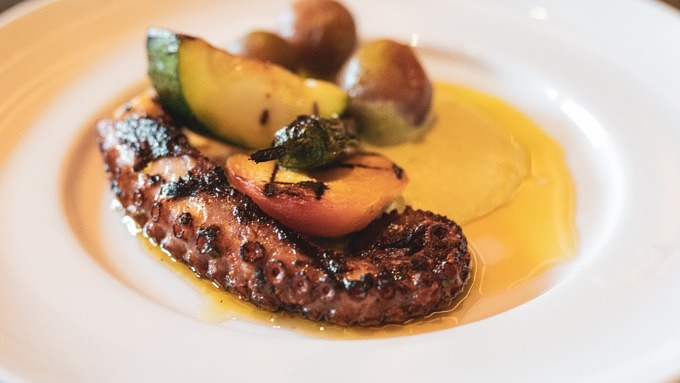 Gegrillter Oktopus mit Gemüse auf einem weißen Teller