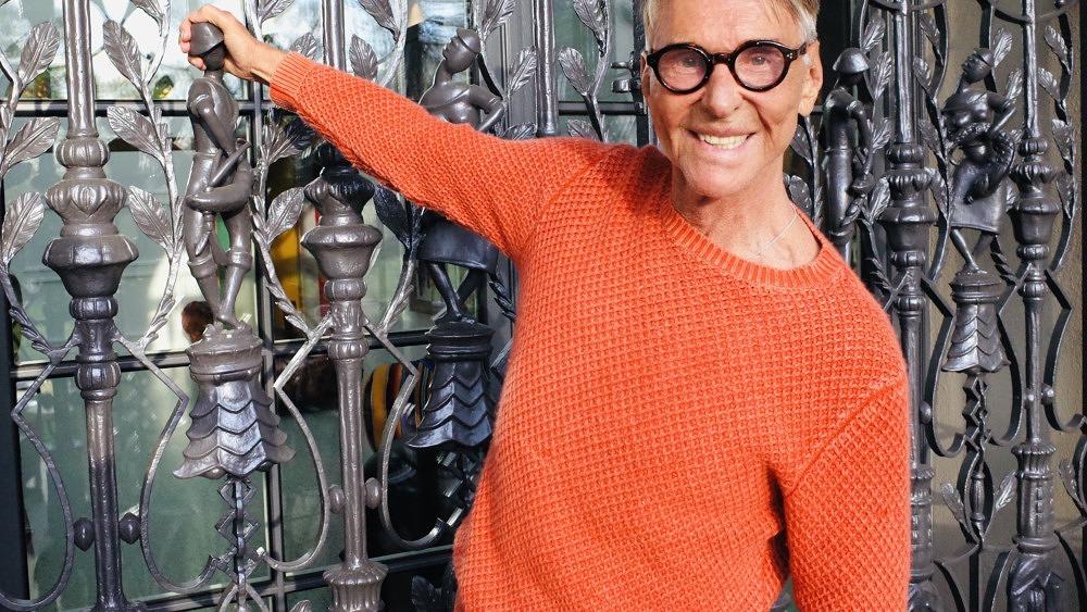 Wolfgang Joop hält sich an einem Tor fest und lächelt in die Kamera. Er trägt einen orangenen Pullover und eine Brille.