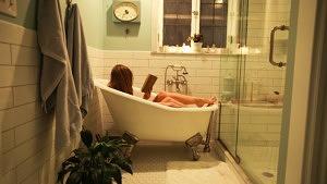 Eine Frau liegt in einer kleinen Badewanne und liest ein Buch